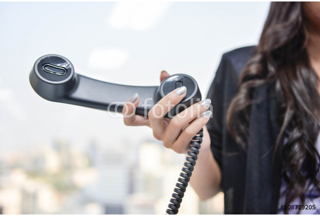 Obraz nowoczesny Business woman is holding the IP Phone handset 64239