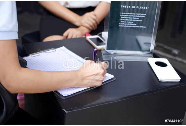Businesswoman's hand with pen completing information form 64239