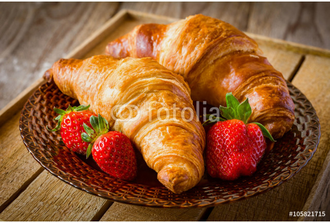 Two croissants and fresh strawberries on brown plate on rustic wooden background. Freshly baked french pastry and berries for breakfast 64239
