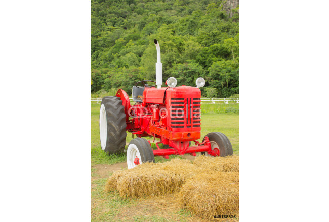 An old red retro tractor in a field 64239