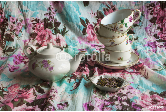 Kettle, set different cups, tea with flowers of heather on fabric background with floral pattern 64239