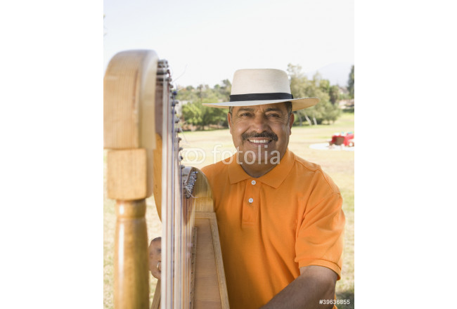 Middle-aged Hispanic man playing harp outdoors 64239