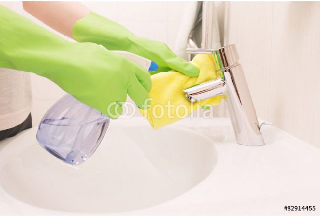 Woman doing chores in bathroom, cleaning sink and faucet with sp 64239