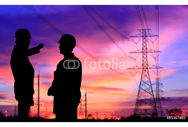 silhouette of two engineers standing at electricity station, discussing plan 64239