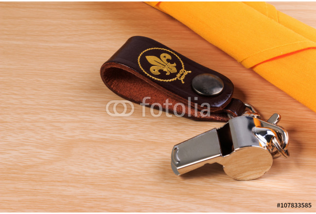 Obraz nowoczesny Metal whistle with yellow scout scarf on wooden background. 64239