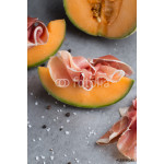 Jambon mix. Ham. Traditional Italian and Spanish salting, smoking, dry-cured dish - jamon Serrano and prosciutto crudo sliced with melon on grey background. Copy space. Closeup. 64239