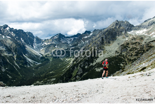 ultra trail runner training for fitness in high mountain scenery with peak view 64239