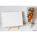 Empty canvas on a white table and a pot of flowers 64239