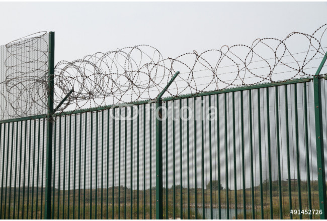 Green fence with razor wire guarding French ferry terminal. 64239