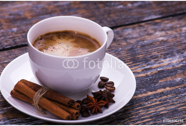 Coffee cup and beans on a wooden table. Dark background. 64239