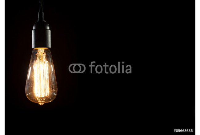 A classic Edison light bulb on black background with space for text 64239