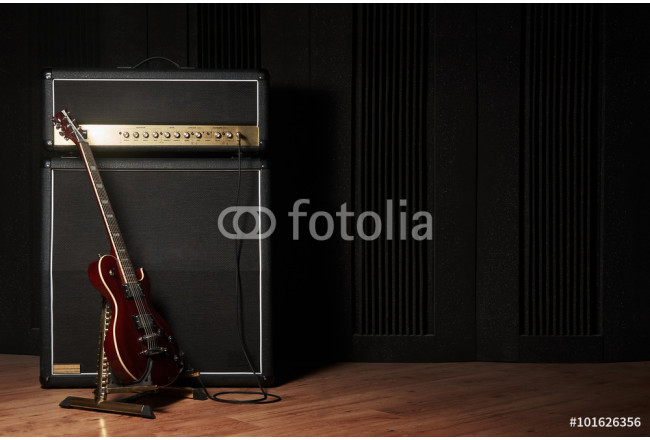 Red electric guitar and classic amplifier on a dark background 64239