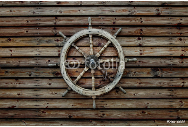 Steering wheel of the ship on a wooden wall 64239