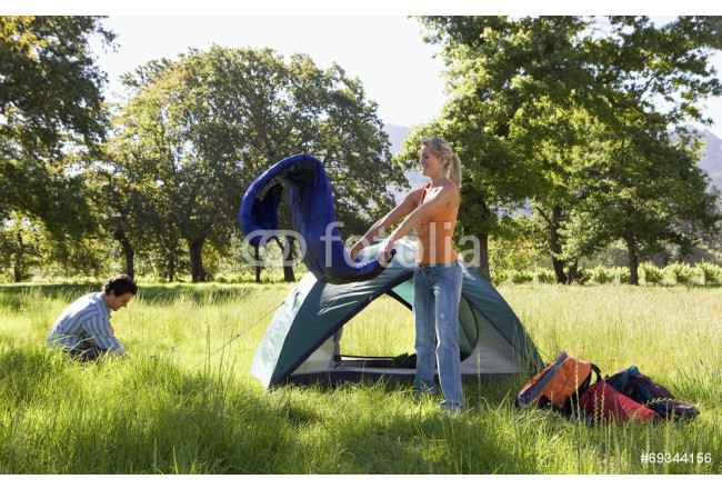 Young couple setting up camp in woodland clearing, woman unravelling rolled-up sleeping bag beside tent, side view 64239