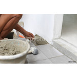 Man troweling mortar on a floor  for laying tile 64239
