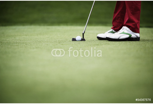 Close-up of golfer putting 64239