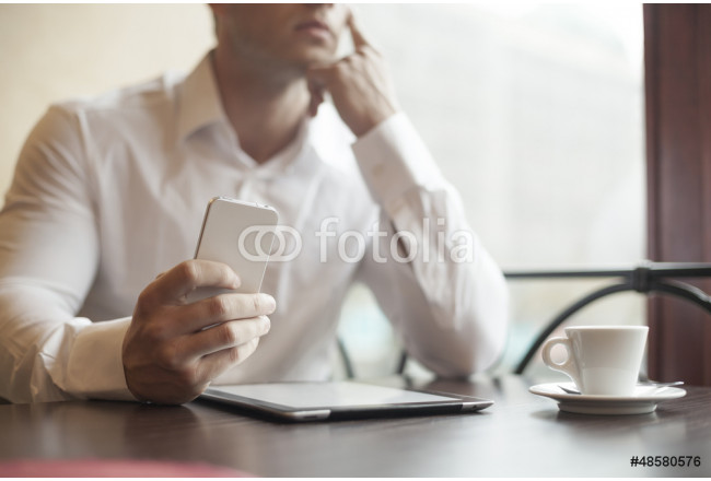 Businesman with smartphone in cafe 64239