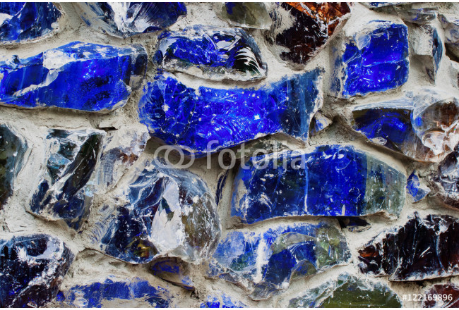 Abstract wallpaper texture of real walls, bright color. Blue , with colored stone and glass in a concrete gray wall. 64239
