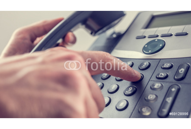 Man dialling out on a landline telephone 64239