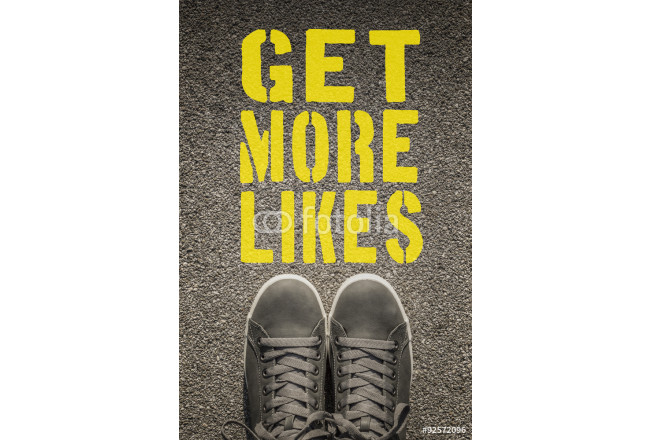 Sneakers with Get More Likes written on the asphalt road 64239