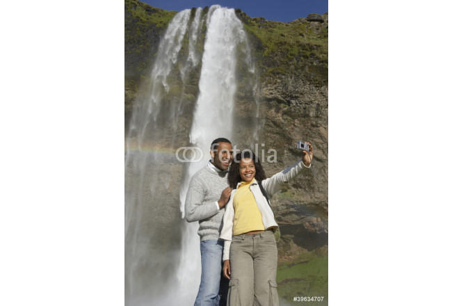 Couple taking own photograph with waterfall 64239