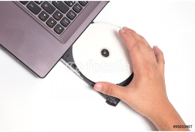 Hand holding New CD/DVD inside optical disk drive bay 64239