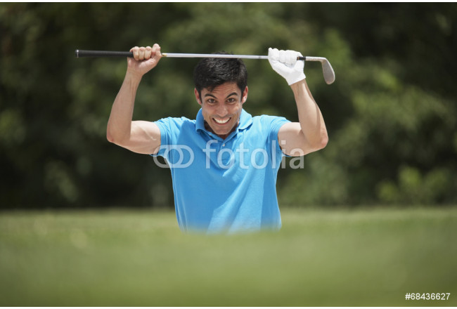 Frustrated Hispanic man holding golf club 64239
