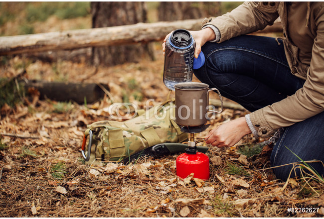 woman pours water from a bottle into a mug 64239