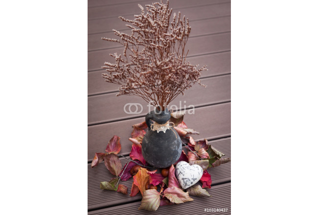 Black ceramic vase with autumn flowers on wooden groung 64239