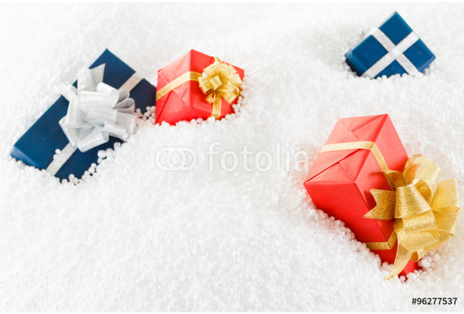 Obraz nowoczesny Decorative blue and red gift box in the snow. 64239