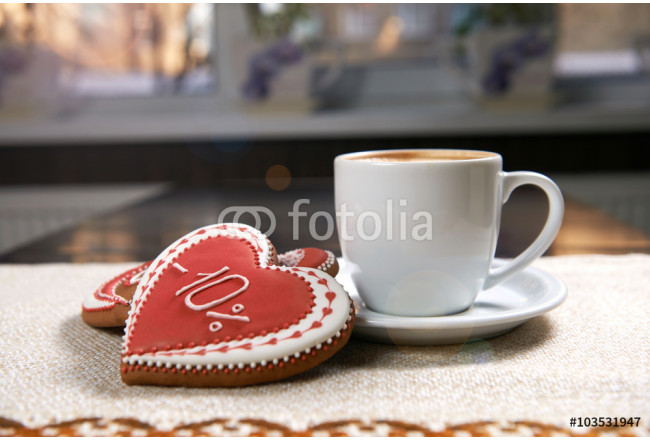 Sunny morning. Shot of a cup of warm coffee with heart shaped red cookie on the table in sunlight beams 64239