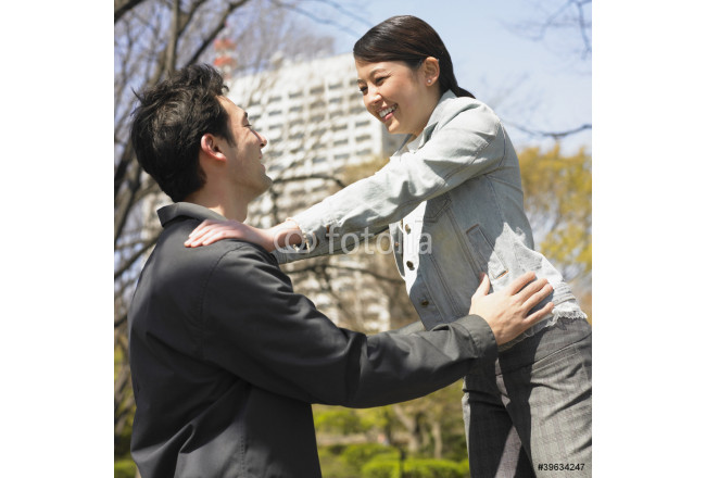 Asian couple laughing smiling at each other urban park 64239