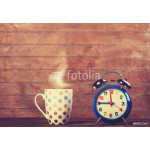 Cup of coffee and alarm clock on wooden table. 64239