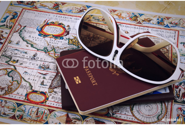 Sun glasses, passports and vintage map on a table. 64239
