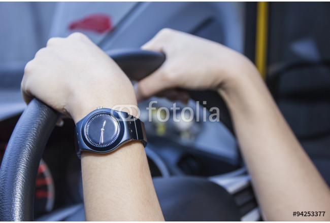 Woman's hands on the steering wheel of the car. 64239