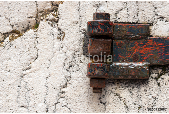 Rusty Hinge on white Rock / Detail of an old rusty hinge with big bolts on a white rock 64239