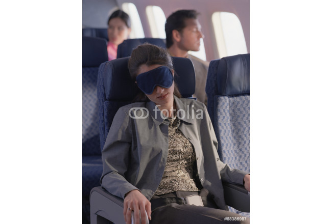 Young woman sleeping on airplane with eye mask 64239