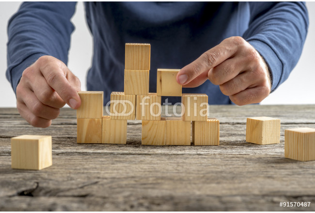 Man Assembling Wooden Cubes on Table 64239