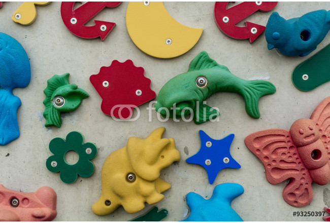 3D shapes and icons on a wall, some with climbing hand holds 64239