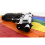still life with close up gun resting on gay parade flag representing sexual discrimination and intolerance 64239