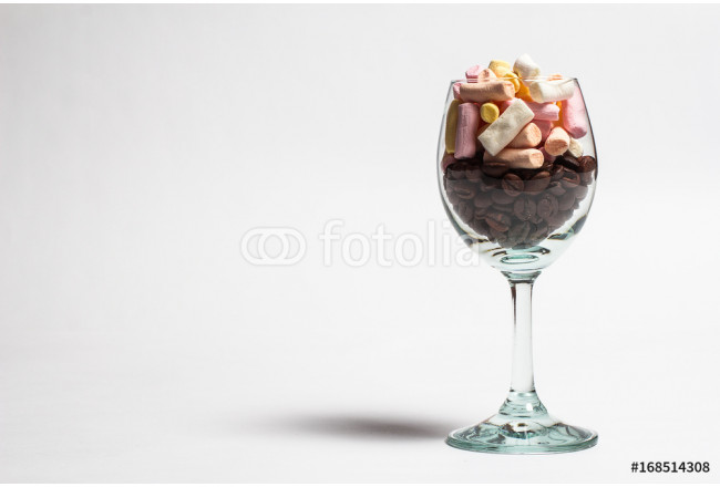 Glass with coffee beans and sweet marshmallows on a white background 64239