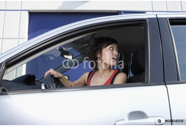 Asian woman looking over shoulder in car 64239