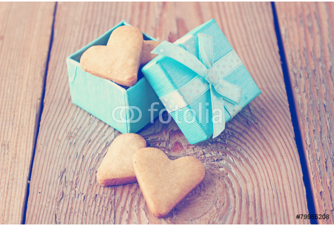 Heart shaped cookies in a blue gift box on a wooden background 64239