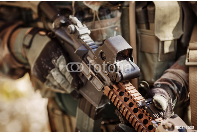 solder in gloves holding assault automatic rifle 64239