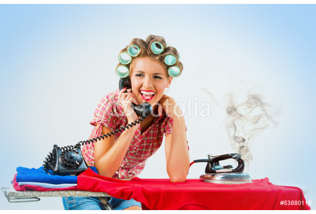 Housewife talking on the phone while ironing, blue background 64239