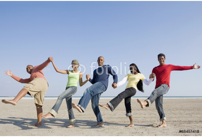 Multi-ethnic friends holding hands and kicking 64239