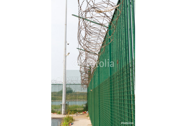 Razor wire on top of green fence guarding French ferry terminal. 64239
