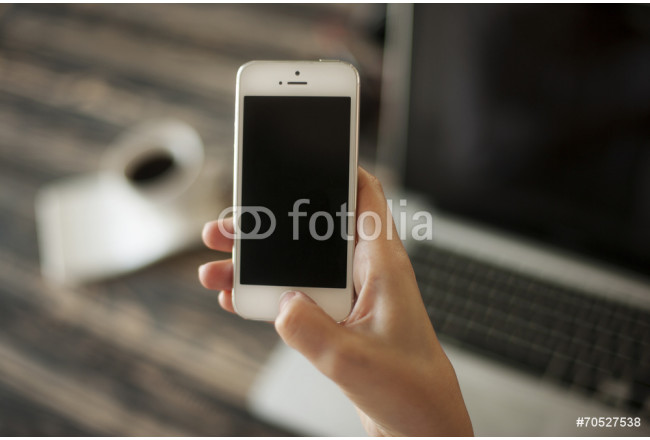 Woman hand holding mobile phone, and laptop and coffee cup in ba 64239