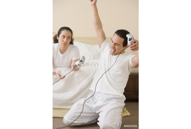 Hispanic couple playing video games in the bedroom 64239