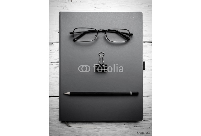 Notepad, eyeglasses, paperclip and pencil on wooden table. Black 64239